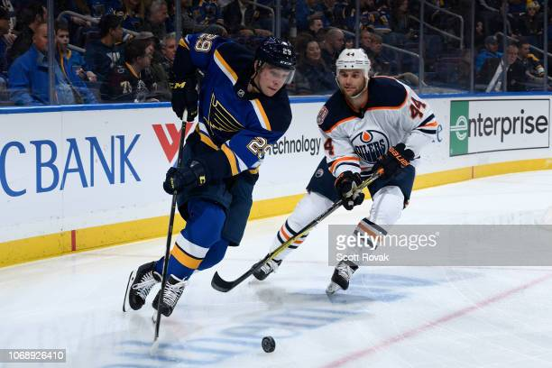 Vince Dunn of the St Louis Blues controls the puck as Zack Kassian of the Edmonton Oilers defends at Enterprise Center on December 5 2018 in St Louis...