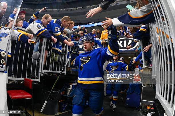Vince Dunn of the St. Louis Blues high fives fans as he takes the ice for warmups against the Colorado Avalanche at Enterprise Center on October 17,...
