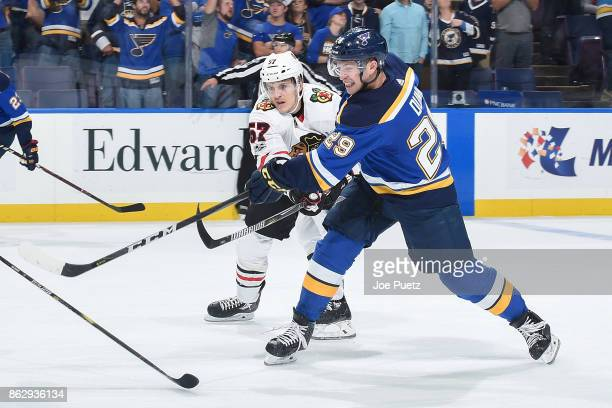 Vince Dunn of the St Louis Blues is defended by Tommy Wingels of the Chicago Blackhawks as he takes a shot at Scottrade Center on October 18 2017 in...