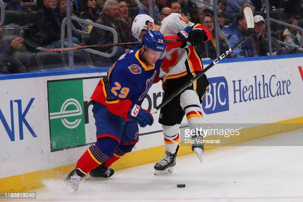 Vince Dunn of the St. Louis Blues knocks Derek Ryan of the Calgary Flames off the puck at Enterprise Center on November 21, 2019 in St Louis,...