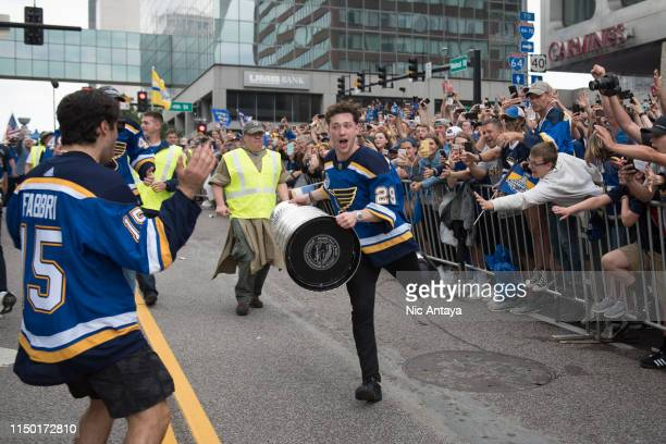 Vince Dunn of the St. Louis Blues runs with the Stanley Cup during the St Louis Blues Victory Parade and Rally after winning the 2019 Stanley Cup...