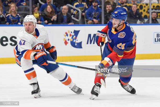 Vince Dunn of the St Louis Blues shoots and scores a goal as Leo Komarov of the New York Islanders attempt to block at Enterprise Center on February...