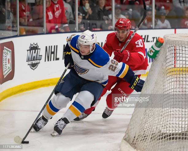 Vince Dunn of the St. Louis Blues skates around the net with the puck in front of Joe Veleno of the Detroit Red Wings in the second period during a...