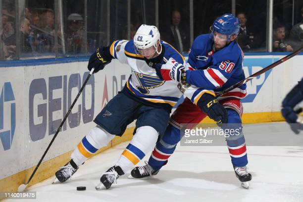 Vince Dunn of the St Louis Blues skates with the puck against Lias Andersson of the New York Rangers at Madison Square Garden on March 29 2019 in New...