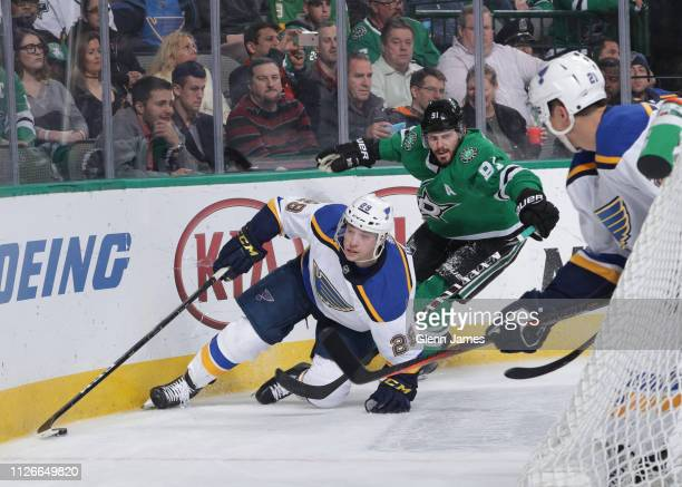 Vince Dunn of the St. Louis Blues tries to keep the puck away against Tyler Seguin of the Dallas Stars at the American Airlines Center on February...