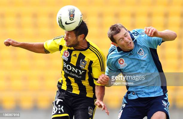 Vince Lia of the Phoenix heads the ball under pressure from Brett Emerton of Sydney FC during the round 13 midweek ALeague match between Wellington...