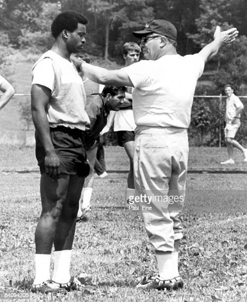 Vince Lombardi the new head coach and general manager of the Washington Redskins works with rookie running back Larry Brown at the Redskins training...
