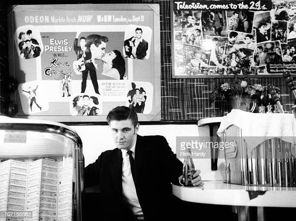 Vince Taylor poses for a portrait next to the jukebox at the 2Is Coffee Bar in Soho circa 1958 Behind him is a poster for the Elvis Presley film King...