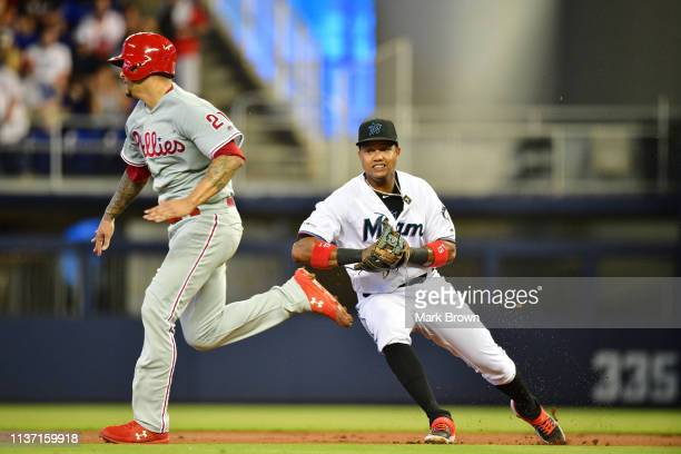 Vince Velasquez of the Philadelphia Phillies avoids the tag of Starlin Castro of the Miami Marlins in the third inning at Marlins Park on April 14...