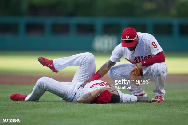 Vince Velasquez of the Philadelphia Phillies lays on the ground after being hit by a ball as Jesmuel Valentin checks on him in the top of the second...