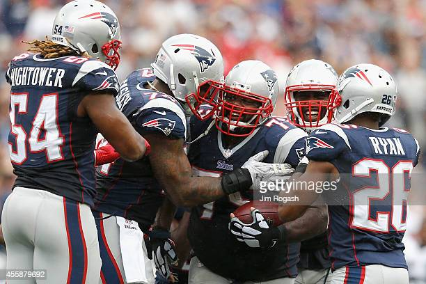 Vince Wilfork of the New England Patriots celebrates with teammates after intercepting the ball during the fourth quarter against Oakland Raiders at...
