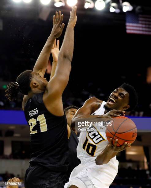 Vince Williams of the Virginia Commonwealth Rams attempts a shot against Chad Brown of the UCF Knights in the first half during the first round of...