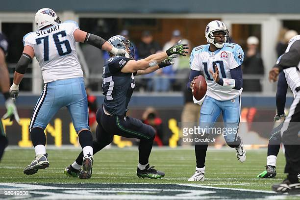Vince Young of the Tennessee Titans looks for a receiver while being pressured by Patrick Kerney of the Seattle Seahawks as David Stewart blocks on...