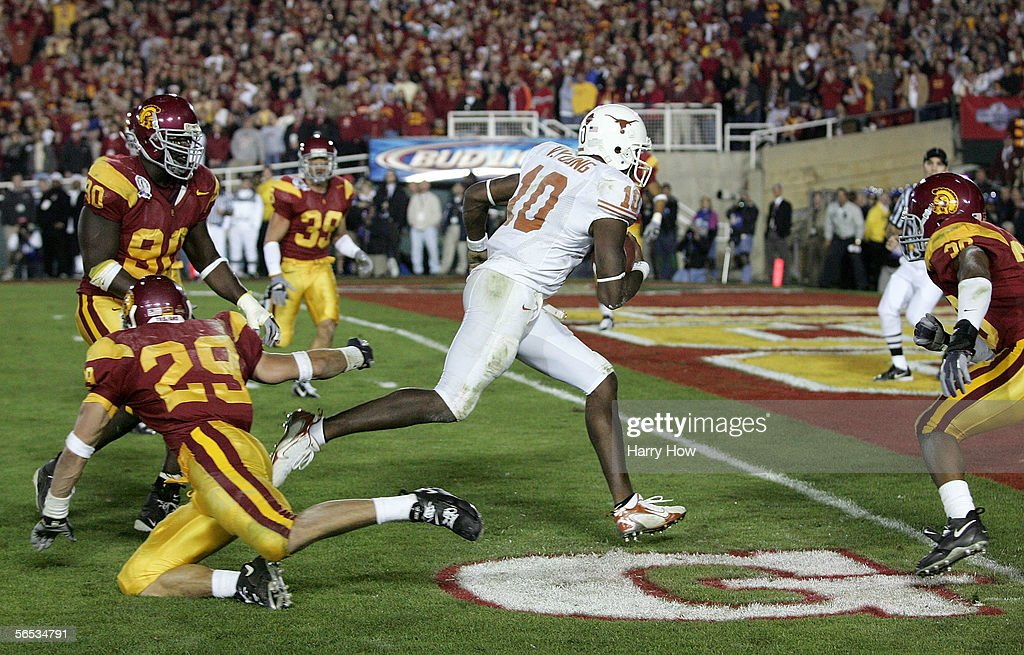 Vince Young #10 of the Texas Longhorns rushes past Frostee Rucker #90, Scott Ware #29 and Josh Pinkard #36 of the USC Trojans to score a 2 point conversion following his touchdown in the final moments of the BCS National Championship Rose Bowl Game at the Rose Bowl on January 4, 2006 in Pasadena, California. Texas defeated USC