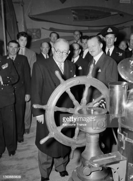 Vincent Auriol et Duff Cooper, l'ambassadeur britannique, devant la barre à roue d'un navire anglais lors de leur visite du Salon nautique en 1947 à...
