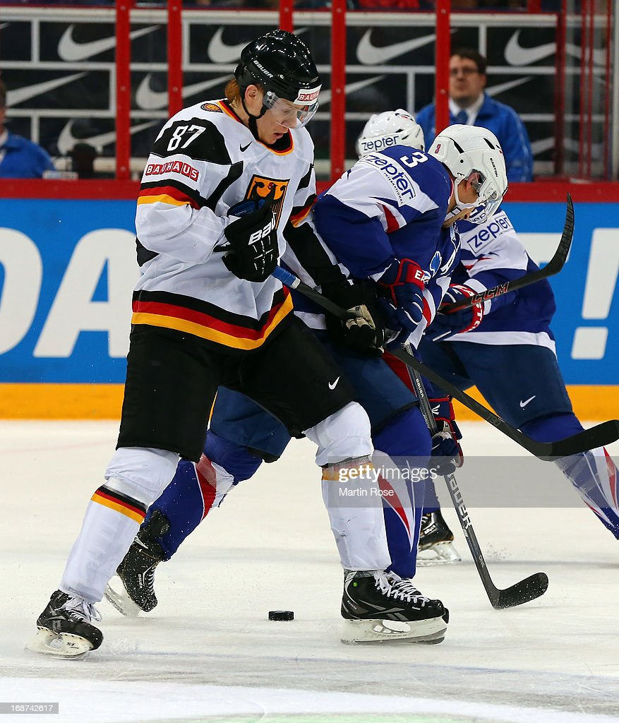 Vincent Bachet (R) of France and Philip Gogulla (L) of Germany battle for the puck during the IIHF World Championship group H match between France and Germany at Hartwall Areena on May 14, 2013 in Helsinki, Finland.