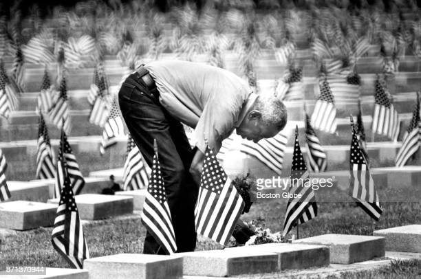 Vincent Coleman places flower pots at the grave site of his father WWII veteran Parker Coleman at the Mount Hope Cemetery in Boston on May 25 1991