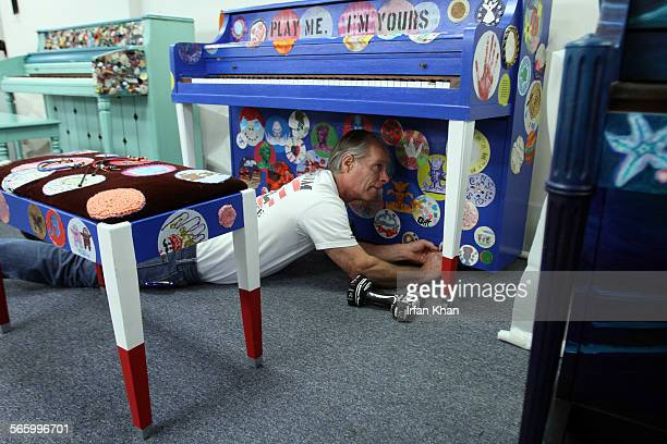 Vincent Collins fixes one of many colorfully painted pianos at LA Chamber Orchestra in Los Angeles For the next three weeks 30 colorful pianos will...