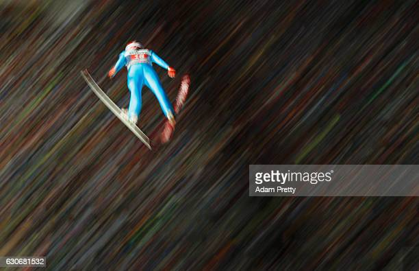 Vincent Descombes Sevoie of France soars through the air during his second competition jump on Day 2 of the 65th Four Hills Tournament ski jumping...