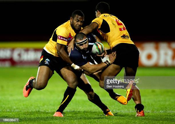 Vincent Duport of France is tackled by Isreal Eliab and Nene McDonald of Papua New Guinea during the Rugby World Cup Group B match between Papua New...