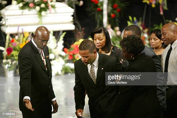 Vincent Edward Brothers is shown to his seat at the funeral for his estranged wife their children and her mother who were found shot to death in...