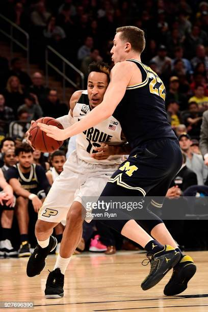 Vincent Edwards of the Purdue Boilermakers drives against Duncan Robinson of the Michigan Wolverines during the championship game of the Big Ten...