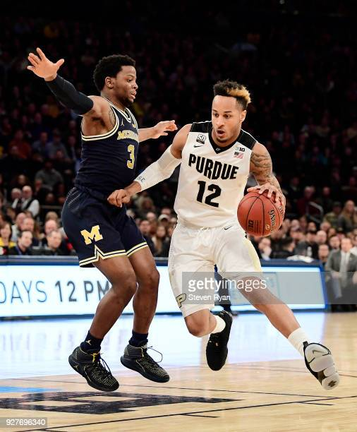 Vincent Edwards of the Purdue Boilermakers drives against Zavier Simpson of the Michigan Wolverines during the championship game of the Big Ten...