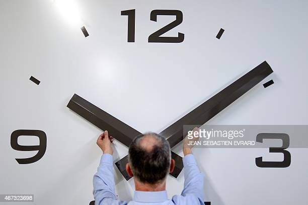 Vincent Girard manager of the 'Girard Le Temps' company adjusts a giant clock on March 20 2015 in Nantes western France The 'Girard Le Temps' company...