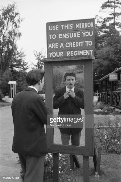 Vincent Jones visits his brother and identical twin Melvyn at a UK army base, 6th August 1958. On the way he adjusts his tie in front of a sign which...
