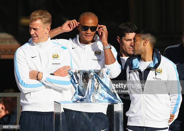 Vincent Kompany Gael Clichy and Joe Hart of Manchester City look on outside Manchester Town Hall at the start of the Manchester City victory parade...