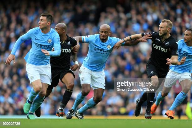 Vincent Kompany of Man City battles with Mike van der Hoorn of Swansea during the Premier League match between Manchester City and Swansea City at...