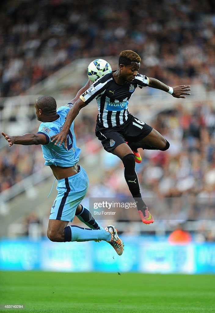 Vincent Kompany of Man City (l) is challenged by Rolando Aarons of Newcastle during the Barclays Premier League match between Newcastle United and Manchester City at St James' Park on August 17, 2014 in Newcastle upon Tyne, England.
