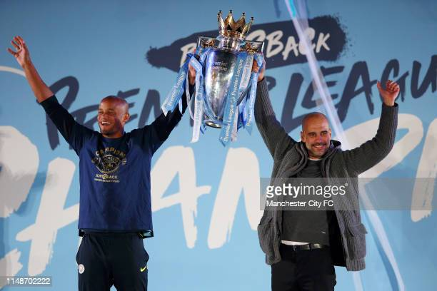 Vincent Kompany of Manchester City and Pep Guardiola, Manager of Manchester City lift the trophy as the celebrate winning the Premier League Title in...