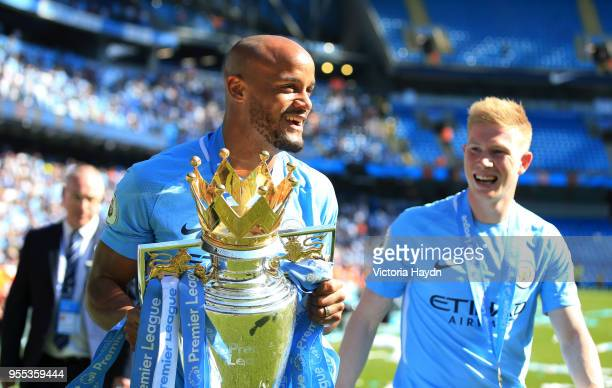 Vincent Kompany of Manchester City celebrate with The Premier League Trophy and Alexander Zinchenko of Manchester City during the Premier League...