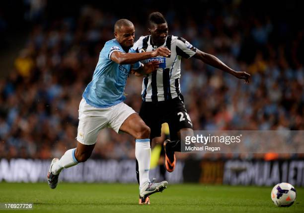 Vincent Kompany of Manchester City challenges Sammy Ameobi of Newcastle United during the Barclays Premier League match between Manchester City and...