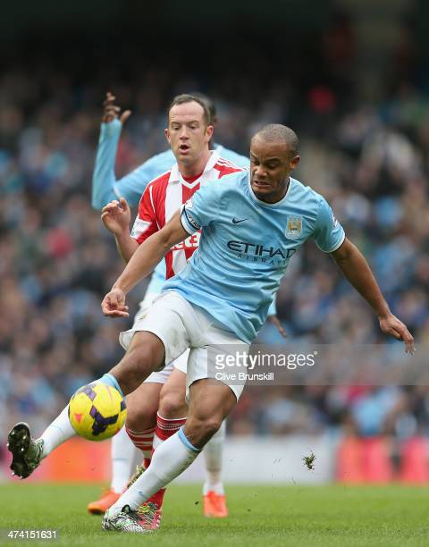 Vincent Kompany of Manchester City holds off a challenge from Charlie Adam of Stoke City during the Barclays Premier League match between Manchester...