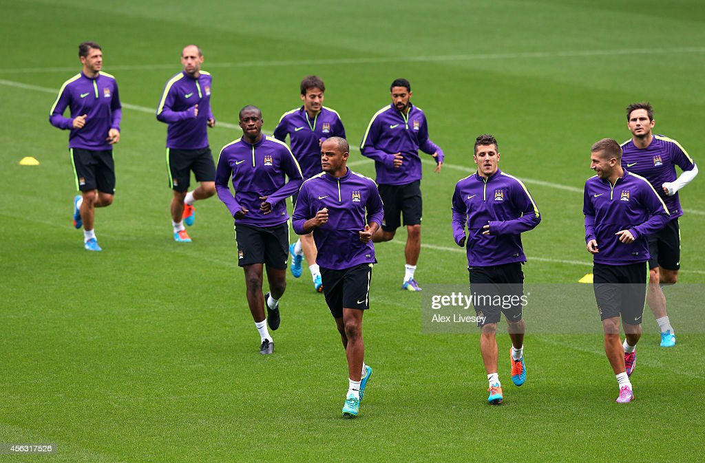 Vincent Kompany of Manchester City leads the warm up during a training session at the Etihad Stadium on September 29, 2014 in Manchester, England.