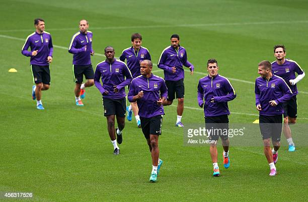 Vincent Kompany of Manchester City leads the warm up during a training session at the Etihad Stadium on September 29 2014 in Manchester England