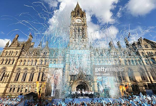 Vincent Kompany of Manchester City lifts the Barclays Premier League trophy aloft outside Manchester Town Hall at the start of the Manchester City...