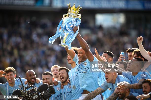 Vincent Kompany of Manchester City lifts the English Premier League Trophy as they celebrate becoming champions after the Premier League match...