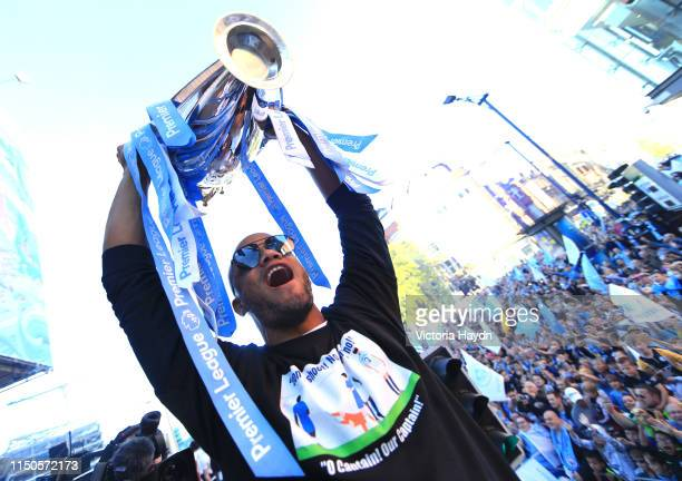Vincent Kompany of Manchester City lifts the Premier League trophy from a parade bus during the Manchester City Teams Celebration Parade on May 20,...