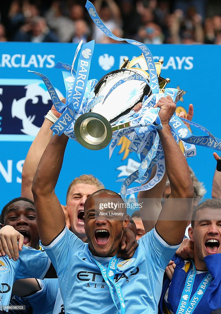 Vincent Kompany of Manchester City lifts the Premier League trophy at the end of the Barclays Premier League match between Manchester City and West Ham United at the Etihad Stadium on May 11, 2014 in Manchester, England.