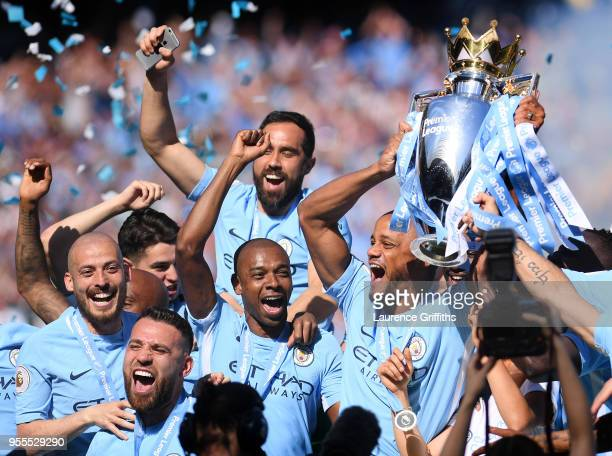 Vincent Kompany of Manchester City lifts the Premier League Trophy alongside David Silva Nicolas Otamendi and Fernandinho as Manchester City...