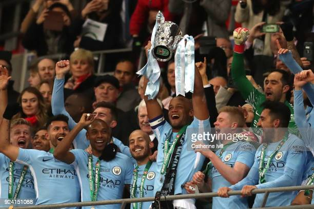 Vincent Kompany of Manchester City lifts the trophy and celebratesd with team mates after winning the Carabao Cup Final between Arsenal and...