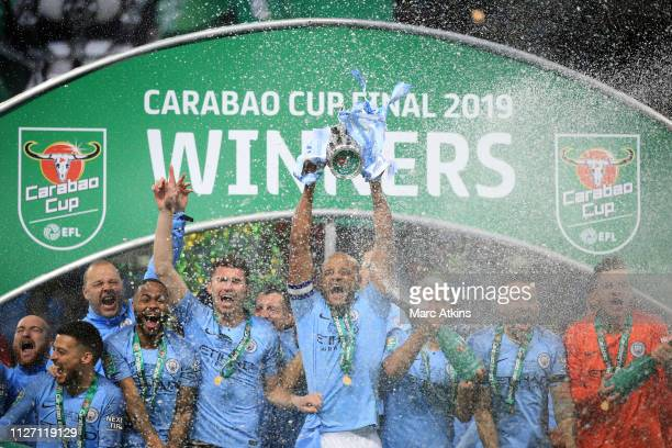 Vincent Kompany of Manchester City lifts the trophy surrounded by team mates during the Carabao Cup Final between Chelsea and Manchester City at...