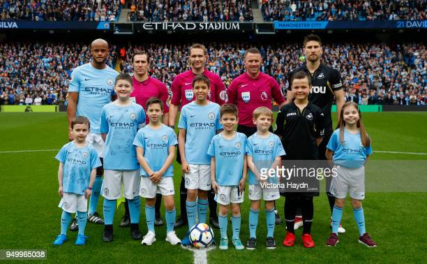 Vincent Kompany of Manchester City Match Officials and Federico Fernandez of Swansea City line up with the team mascots ahead of the Premier League...