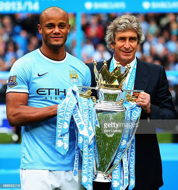 Vincent Kompany of Manchester City poses with manager Manuel Pellegrini and the Barclays Premier League trophy after the Barclays Premier League...