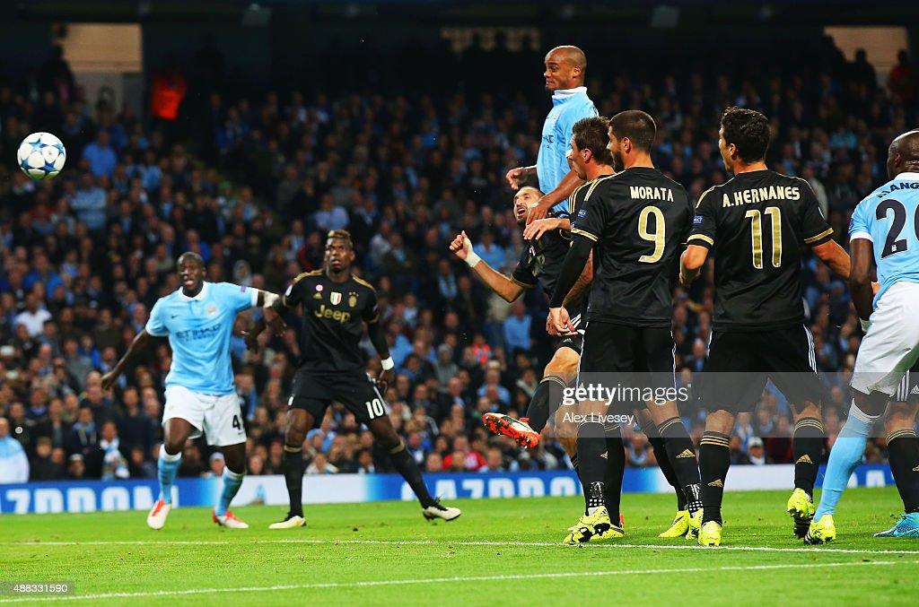 Vincent Kompany of Manchester City (4L) pressures Giorgio Chiellini of Juventus (3L) into scoring an own goal for their first during the UEFA Champions League Group D match between Manchester City FC and Juventus at the Etihad Stadium on September 15, 2015 in Manchester, United Kingdom.