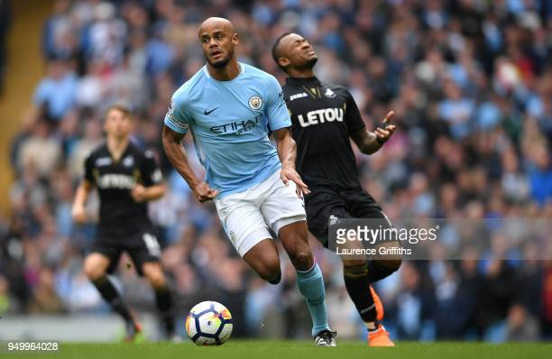 Vincent Kompany of Manchester City runs with the ball whilst Jordan Ayew of Swansea City reacts during the Premier League match between Manchester...