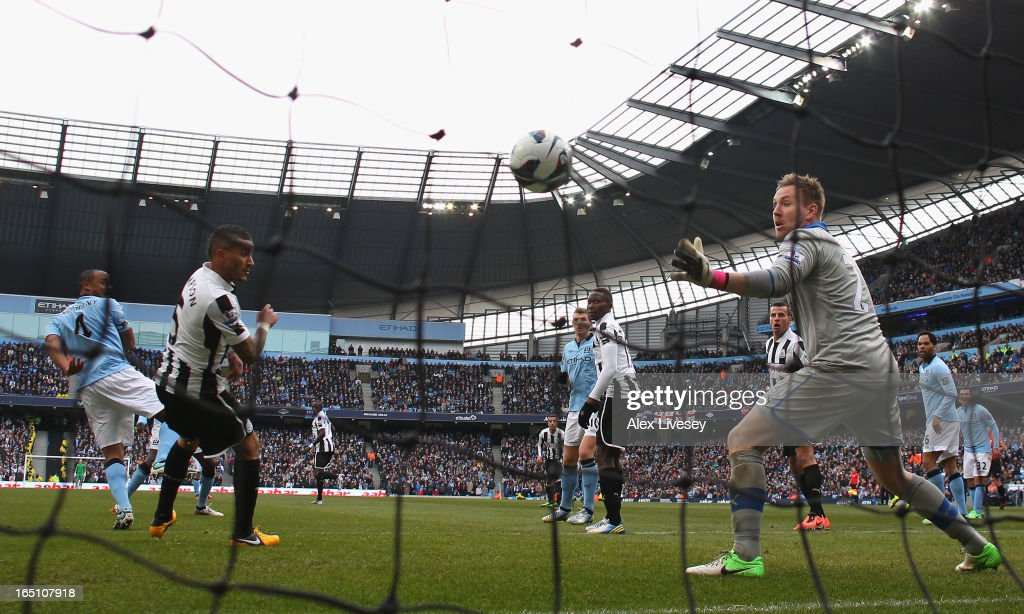 Vincent Kompany of Manchester City scores his team's third goal past Rob Elliot of Newcastle United during the Barclays Premier League match between Manchester City and Newcastle United at the Etihad Stadium on March 30, 2013 in Manchester, England.